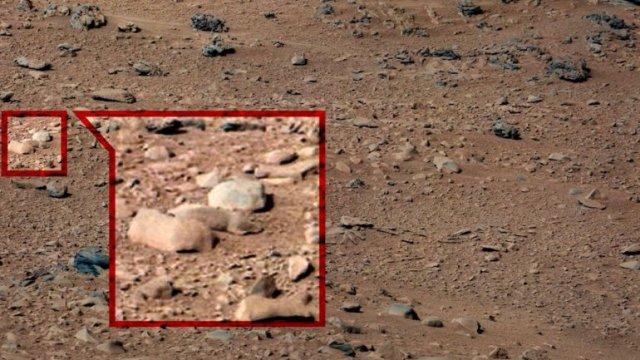 La ardilla agachada en dos rocas