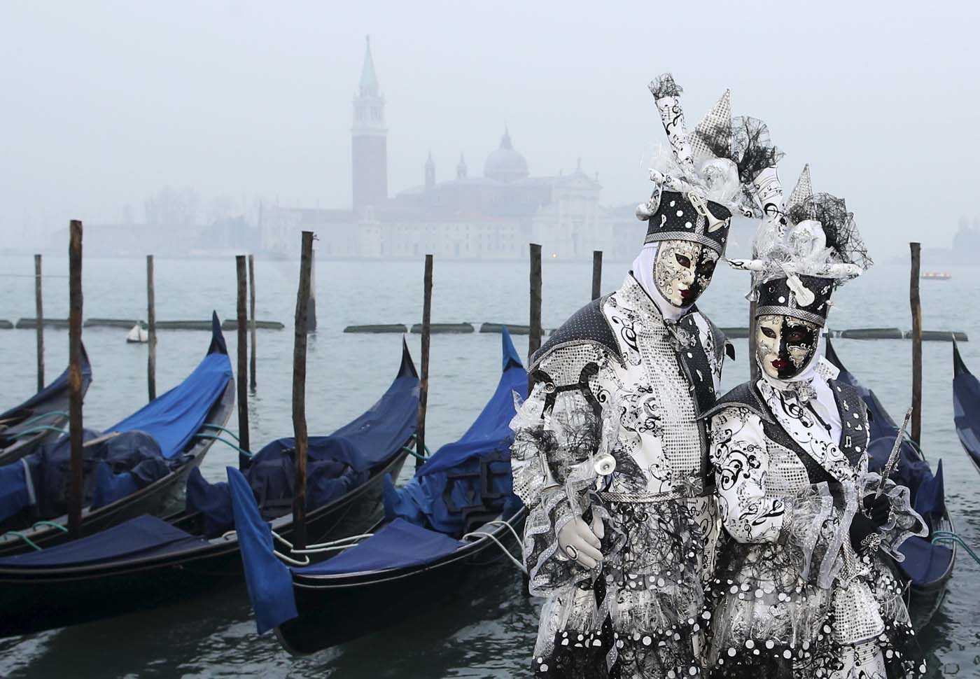 Masked revellers pose during the Venice Carnival, in San Marco Piazza January 30, 2016. REUTERS/Alessandro Bianchi