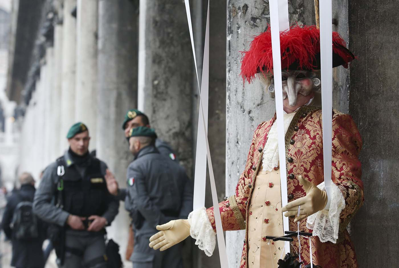 A masked reveller (R) poses in San Marco Piazza next to Italian Finance Police personnel during the Venice Carnival, January 30, 2016. REUTERS/Alessandro Bianchi