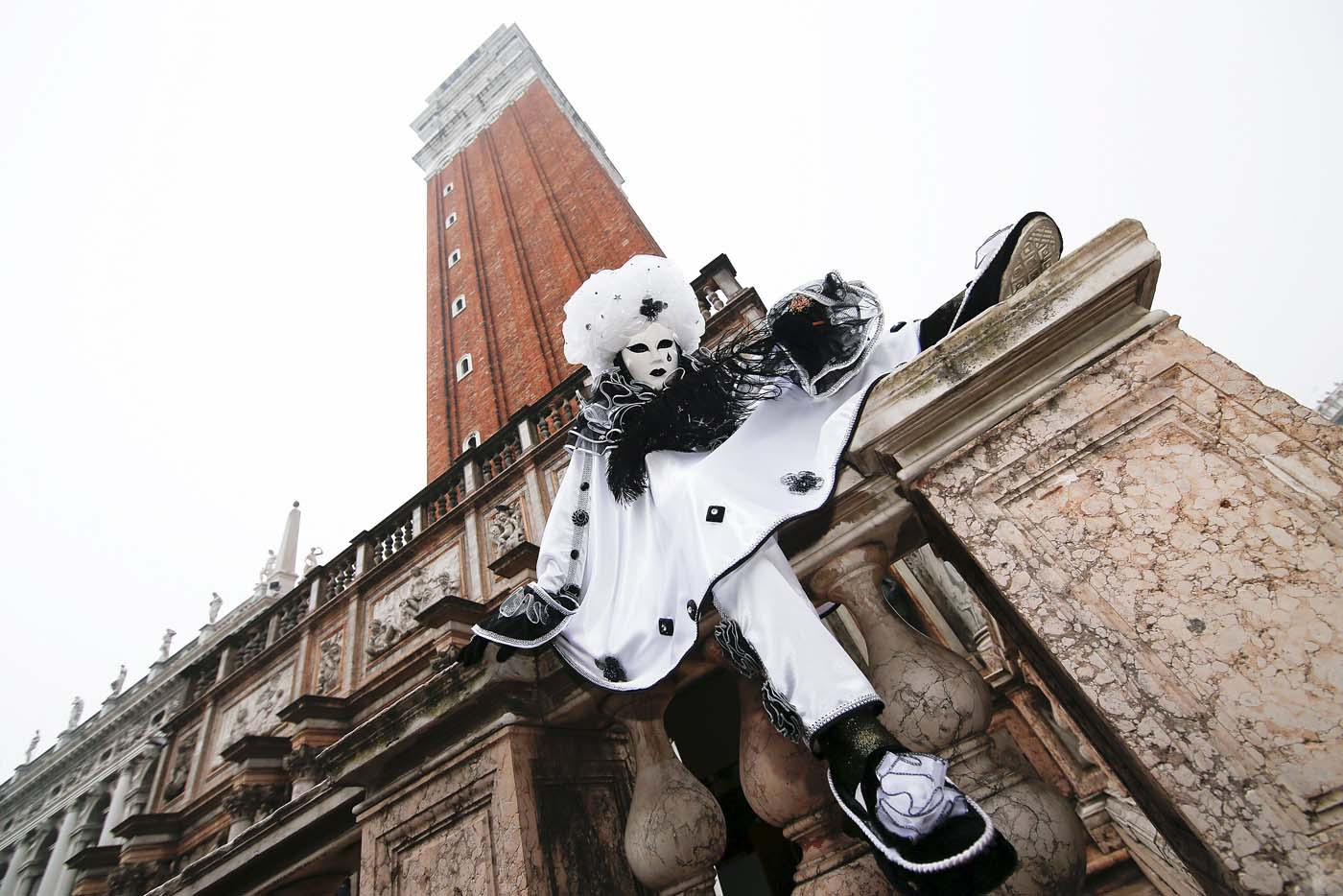 A masked reveller (R) poses in San Marco Piazza during the Venice Carnival, January 30, 2016. REUTERS/Alessandro Bianchi