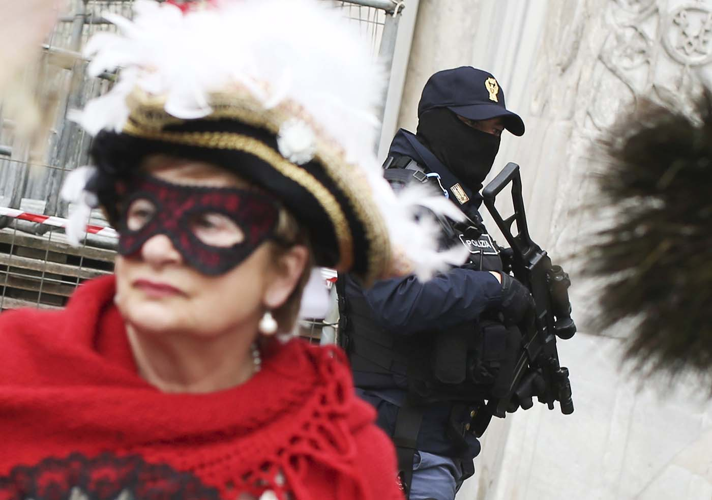 An Italian policeman (R) patrols as masked revellers arrive at San Marco Piazza during the Venice Carnival, January 31, 2016. REUTERS/Alessandro Bianchi