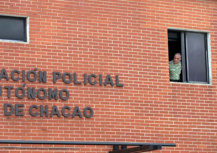 Un agente se asoma desde una ventana en la sede policial de la municipalidad del Chacao en Caracas, Venezuela, el lunes 30 de mayo de 2016. Las autoridades venezolanas dijeron que arrestaron a cuatro hombres por el homicidio del mayor general retirado Félix Velásquez, que fungió como jefe de seguridad del fallecido presidente Hugo Chávez. La procuraduría nacional dijo el lunes que dos de los sospechosos son policías del distrito Chacao de la capital, el cual es gobernado por la oposición. (AP foto/Fernando Llano)
