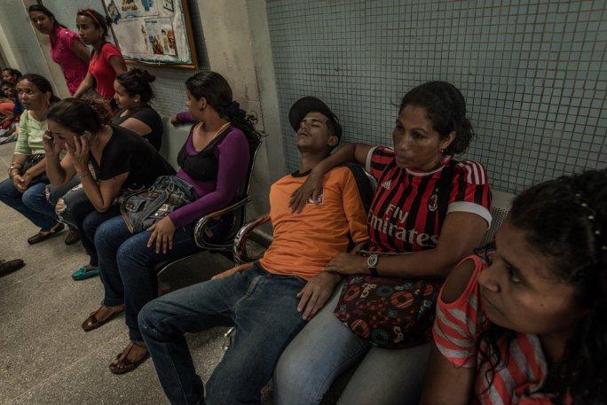 Maribel Supero sostiene a su hijo, un minero ilegal que llevaba 21 días enfermo de malaria. Credit Meridith Kohut para The New York Times