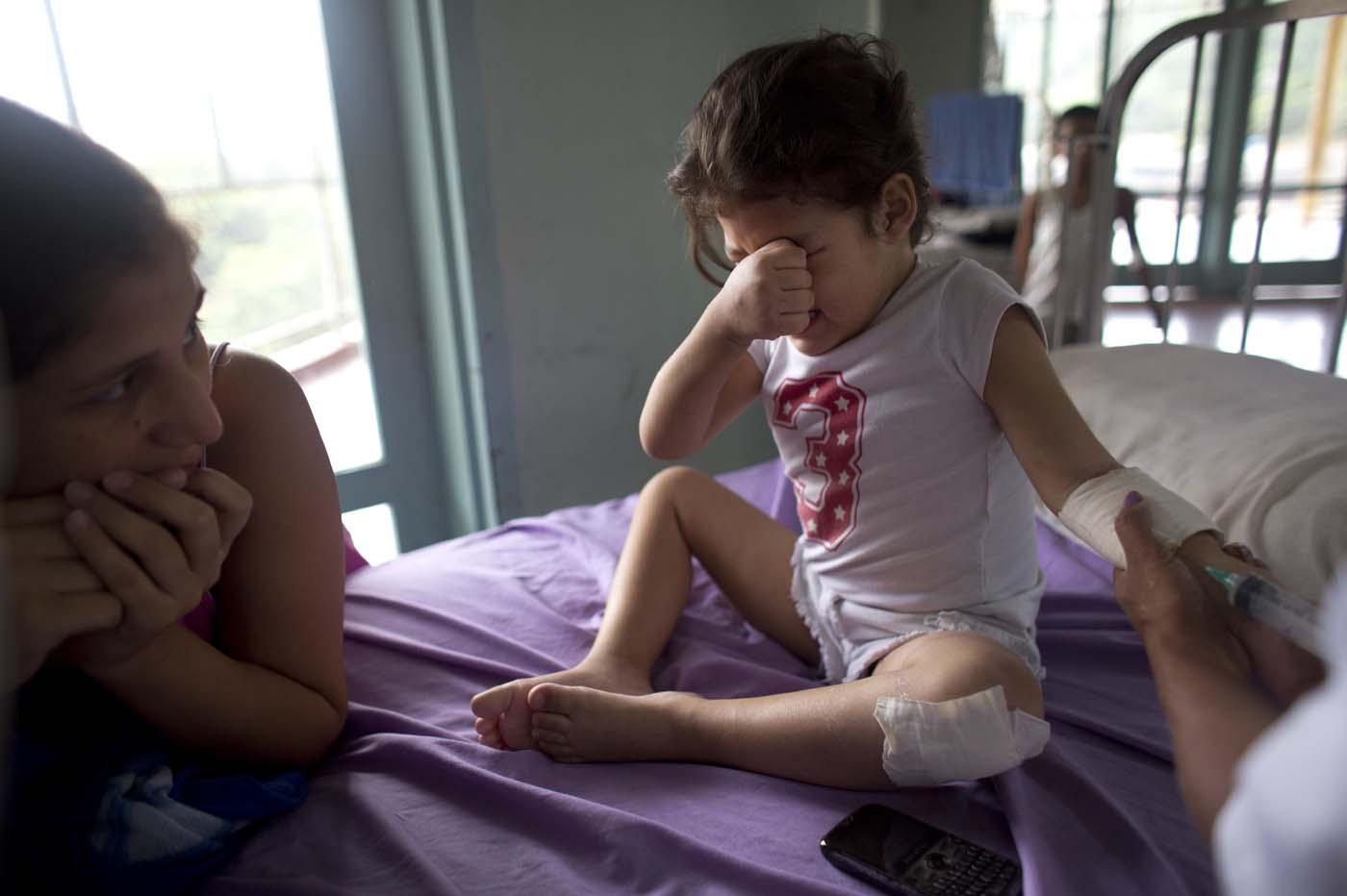 En esta imagen, tomada el 24 de agosto de 2016, Ashley Pacheco, de 3 años, llora mientras recibe una inyección ante la atenta mirada de su madre, en el hospital universitario de Caracas, Venezuela. Dos semanas después de sufrir un raspón en una rodilla, la niña se retorcía de dolor en la cama de un hospital. Le costaba respirar e imploraba a sus padres que le llevasen agua. (AP Foto/Ariana Cubillos)