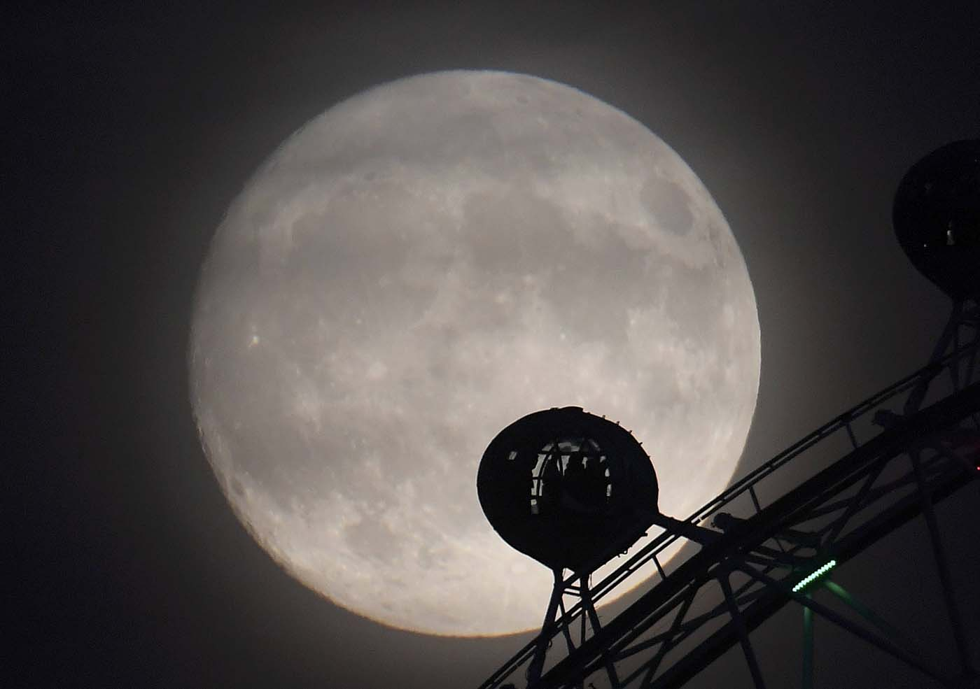 "The moon is seen behind the London Eye wheel a day before the ""supermoon"" spectacle in London, Britain, November 13, 2016. REUTERS/Toby Melville"
