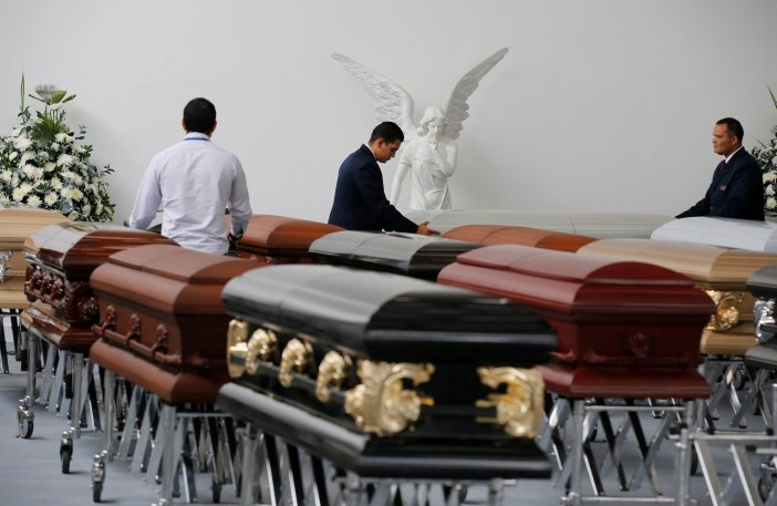 Funeral workers arrange coffins holding the remains of the victims who died in an accident of a plane that crashed into the Colombian jungle with Brazilian soccer team Chapecoense onboard, in Medellin, Colombia December 1, 2016. REUTERS/Jaime Saldarriaga TPX IMAGES OF THE DAY