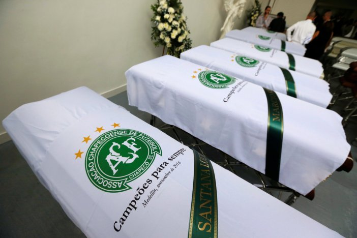 Blankets bearing the crest of Brazilian soccer team Chapecoense are placed on coffins holding the remains of the victims who died in an accident of the plane that crashed into the Colombian jungle with the team's players onboard, in Medellin, Colombia December 1, 2016. REUTERS/Jaime Saldarriaga