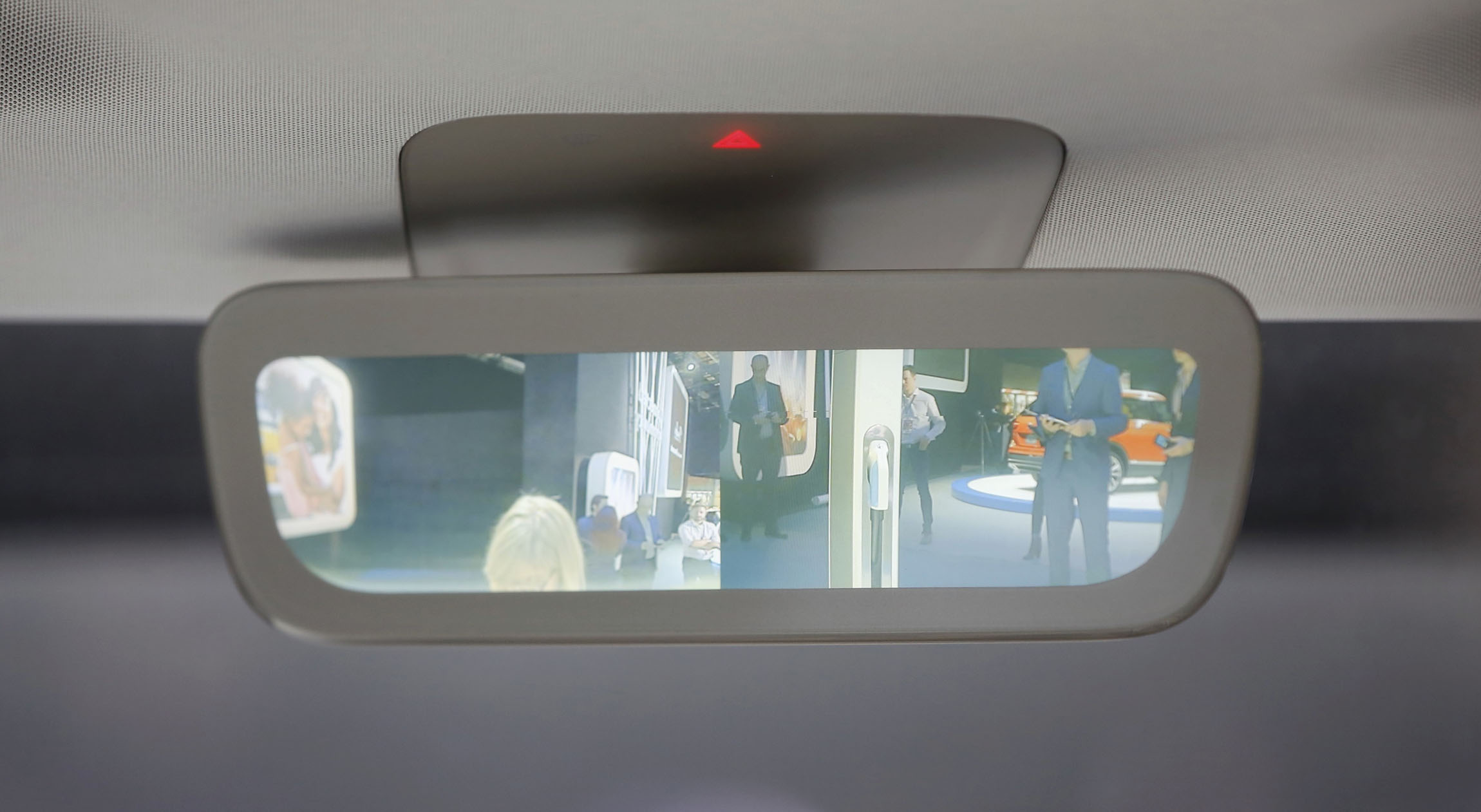 Auto show visitors are seen in the rear view mirror of a Volkswagen I.D. Buzz electric concept vehicle being displayed during the North American International Auto Show in Detroit