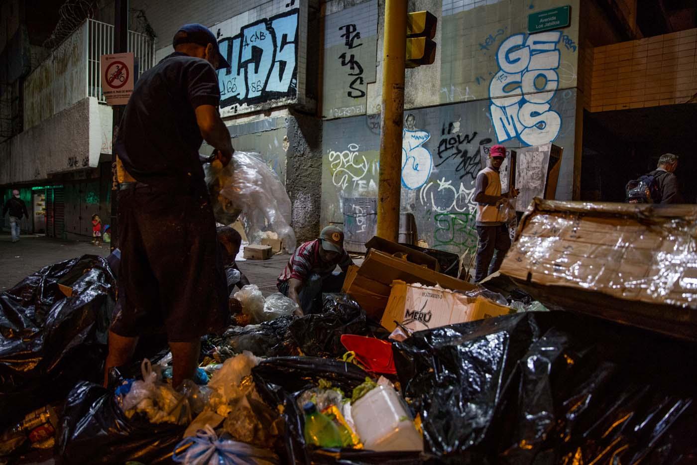 ACOMPAÑA CRÓNICA: VENEZUELA CRISIS. CAR10. CARACAS (VENEZUELA), 31/12/2016.- Varias personas buscan comida entre bolsas de basura este jueves, 31 de diciembre de 2016, en Caracas (Venezuela). La profunda crisis que aqueja a Venezuela trajo como consecuencia escasez y hambre, lo que a su vez ha llevado a familias enteras a buscar restos de alimentos en los basureros y, muchas veces, a pelear con otras personas sin recursos, por un desecho comestible o algún material reciclable que se pueda vender. EFE/Miguel Gutiérrez