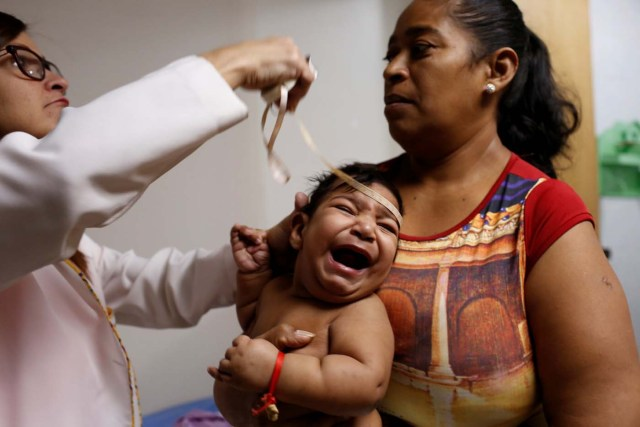 """Iberis Vargas (R), holds her 7-month-old daughter, Geovelis Ramos, a neurological patient being treated with anticonvulsants, while an specialist examines her in a clinic in La Guaira, Venezuela February 4, 2017. REUTERS/Carlos Garcia Rawlins SEARCH """"EPILEPSY CARACAS"""" FOR THIS STORY. SEARCH """"WIDER IMAGE"""" FOR ALL STORIES."""