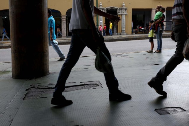 """Norymar Torres (R), holds the hand of her son Lorenzo, 5, and carries her son Leonardo, 6, who is a neurological patient being treated with anticonvulsants, while they wait for transportation on the street in Caracas, Venezuela January 24, 2017. REUTERS/Carlos Garcia Rawlins SEARCH """"EPILEPSY CARACAS"""" FOR THIS STORY. SEARCH """"WIDER IMAGE"""" FOR ALL STORIES."""
