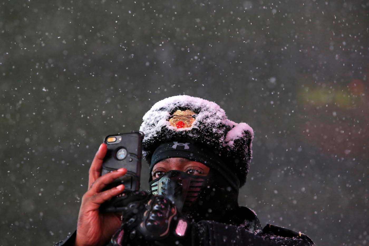 Times Square Public Safety Sergeant Baldwin Davis captures falling snow with his cellular device in Times Square in Manhattan, New York, U.S., March 14, 2017. REUTERS/Andrew Kelly