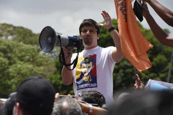 Venezuelan opposition deputy Freddy Guevara -wearing a t-shirt depicting jailed leader Leopoldo Lopez- addresses demosntrators during a protest against the government of President Nicolas Maduro on April 6, 2017 in Caracas. The center-right opposition vowed fresh street protests -after earlier unrest left dozens of people injured - to increase pressure on Maduro, whom they blame for the country's economic crisis. / AFP PHOTO / JUAN BARRETO