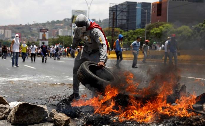 Demonstrators build a fire barricade on a street in Caracas, Venezuela April 10, 2017. REUTERS/Carlos Garcia Rawlins