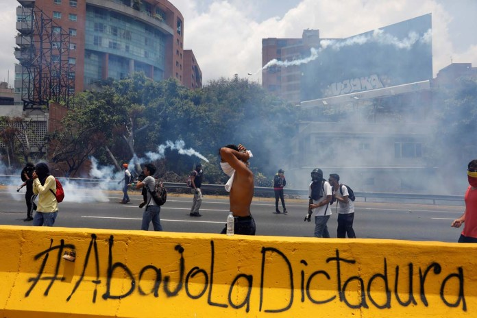 "Demonstrators rally against Venezuela's President Nicolas Maduro's government in Caracas, Venezuela April 10, 2017. The graffiti reads "" Down with the dictatorship"". REUTERS/Carlos Garcia Rawlins"