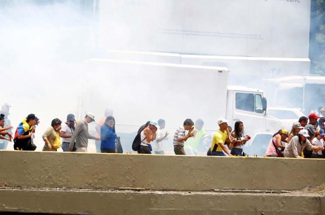 Demonstrators run away from tear gas during a rally against Venezuela's President Nicolas Maduro's government in Caracas, Venezuela April 10, 2017. REUTERS/Christian Veron