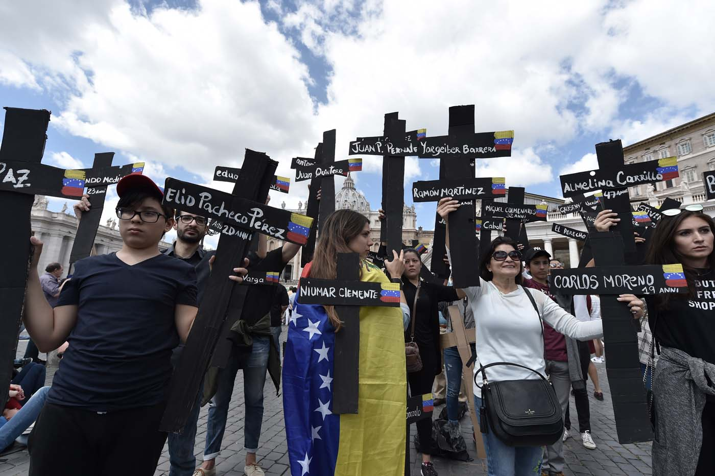 """Members of the Venezuelian community hold black crosses with names of victims of clashes with police during protests against Venezuela's President Nicolas Maduro, on May 7, 2017 at St Peter's square before the Regina Coeli prayer of Pope Francis in Vatican. Pope Francis last week made a heartfelt appeal for """"negotiated solutions"""" to end the violence in crisis-torn Venezuela for the sake of an """"exhausted population"""". The death toll since April -- when the protests intensified after Maduro's administration and the courts stepped up efforts to undermine the opposition -- is at least 36, according to prosecutors, with hundreds more injured. / AFP PHOTO / TIZIANA FABI"""