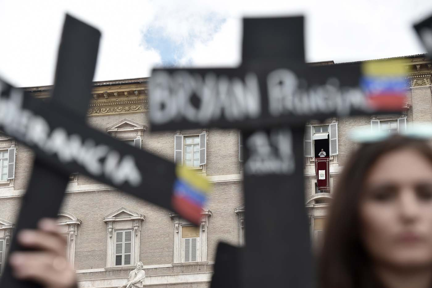 """Members of the Venezuelian community hold black crosses with names of victims of clashes during protests against Venezuela's President Nicolas Maduro, on May 7, 2017 at St Peter's square as Pope Francis stands at the window of the apostolic palace during the Regina Coeli prayer in Vatican. Pope Francis last week made a heartfelt appeal for """"negotiated solutions"""" to end the violence in crisis-torn Venezuela for the sake of an """"exhausted population"""". The death toll since April -- when the protests intensified after Maduro's administration and the courts stepped up efforts to undermine the opposition -- is at least 36, according to prosecutors, with hundreds more injured. / AFP PHOTO / TIZIANA FABI"""