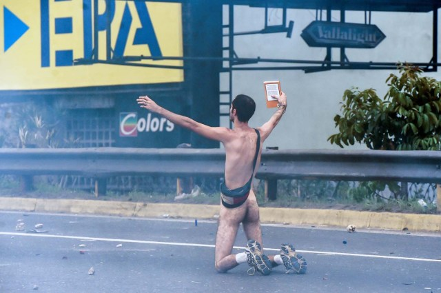 """EDITORS NOTE: Graphic content / (FILES) This file photo taken on April 20, 2017 shows a naked demonstrator taking part in a protest against Venezuelan President Nicolas Maduro, in Caracas on April 20, 2017. Wearing nothing but white sports shoes and socks, a money belt and an anguished expression, Hans Wuerich, 27, raised a bible in his skinny hand as he stood on top of a police armored car on April 20. """"I'm not some flower-power hippy,"""" he told AFP later. """"But I do believe that peaceful protest does more harm to the government than violence. I stunned them.""""  / AFP PHOTO / JUAN BARRETO"""
