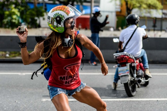 """(FILES) This file photo taken on May 01, 2017 shows an opposition activist throwing a stone during a march against Venezuelan President Nicolas Maduro held on May Day, in Caracas on May 1, 2017. """"That is me all over, the strength and the passion,"""" Ciarcelluti, 44, told AFP. """"I never run out of energy.""""  She says she hopes to be """"an inspiration"""" to other protesters. """"We are getting there,"""" she says.  / AFP PHOTO / FEDERICO PARRA"""