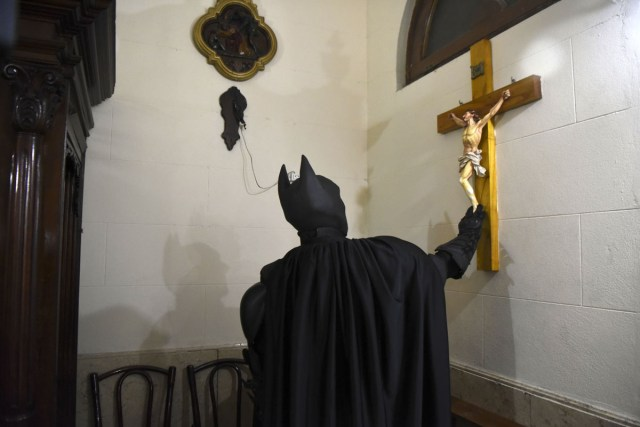 Argentine Batman, prays in a chapel at the 'Sor Maria Ludovica' children's Hospital in La Plata, 60 kilometres south of Buenos Aires, on June 2, 2017.  The Argentine Batman has made La Plata children's hospital a target of laughter and treats against pain. / AFP PHOTO / Eitan ABRAMOVICH