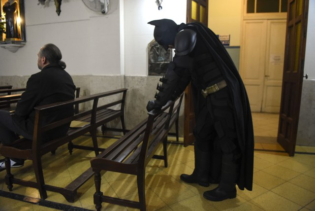 Argentine Batman, makes a stop to pray in a chapel at the 'Sor Maria Ludovica' children's Hospital in La Plata, 60 kilometres south of Buenos Aires, on June 2, 2017.  The Argentine Batman has made La Plata children's hospital a target of laughter and treats against pain. / AFP PHOTO / Eitan ABRAMOVICH