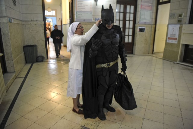 Sister Adriana (L) helps Argentine Batman with his cape at the 'Sor Maria Ludovica' children's Hospital in La Plata, 60 kilometres south of Buenos Aires, on June 2, 2017.  The Argentine Batman has made La Plata children's hospital a target of laughter and treats against pain. / AFP PHOTO / Eitan ABRAMOVICH / TO GO WITH AFP STORY BY PAULA BUSTAMANTE MORE PICTURES IN AFPFORUM