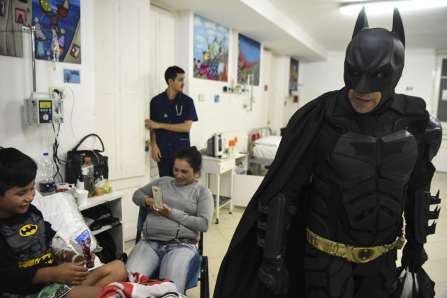 Pablo Valdez (L), 7, who is hospitalized with an infection that prevents him fom walking, is cheered up by Argentine Batman at the 'Sor Maria Ludovica' children's Hospital in La Plata, 60 kilometres south of Buenos Aires, on June 2, 2017.  The Argentine Batman has made La Plata children's hospital a target of laughter and treats against pain. / AFP PHOTO / Eitan ABRAMOVICH