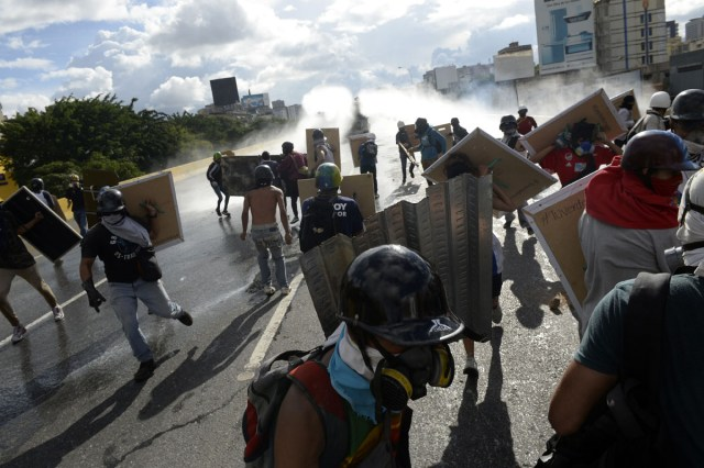 "Opposition demonstrators clash with riot police during the ""Towards Victory"" protest against the government of Nicolas Maduro, in Caracas on June 10, 2017.  Clashes at near daily protests by demonstrators calling for Maduro to quit have left 66 people dead since April 1, prosecutors say.  / AFP PHOTO / FEDERICO PARRA"