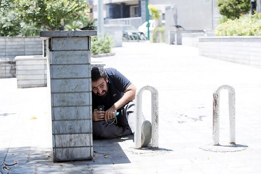A man takes cover during an attack on the Iranian parliament in central Tehran, Iran, June 7, 2017. Tasnim News Agency/Handout via REUTERS ATTENTION EDITORS - THIS PICTURE WAS PROVIDED BY A THIRD PARTY. FOR EDITORIAL USE ONLY. NO RESALES. NO ARCHIVE.