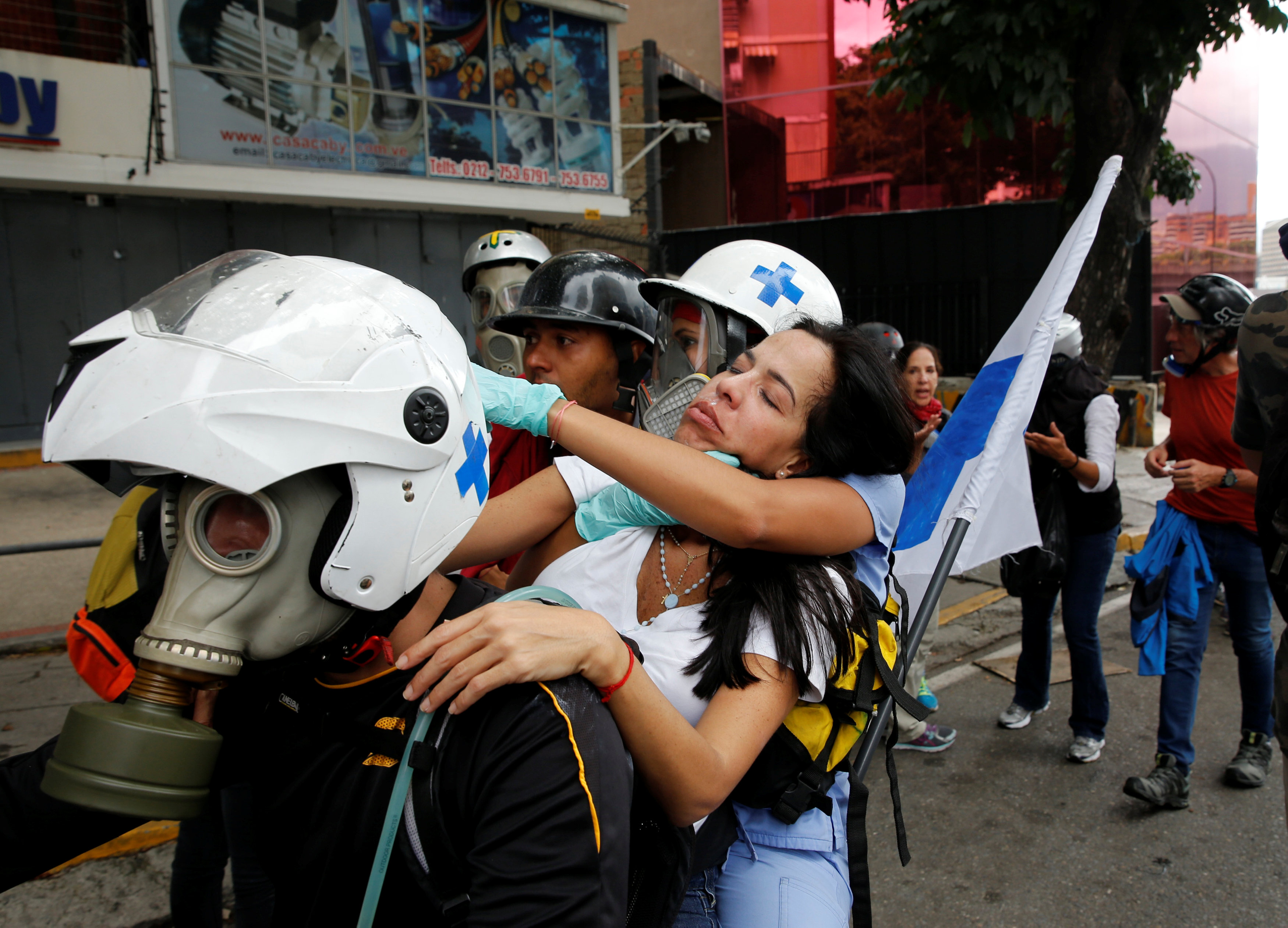 An opposition supporter affected by tear gas is carried away on a motorcycle during a rally against Venezuela's President Nicolas Maduro in Caracas, Venezuela, June 10, 2017. REUTERS/Ivan Alvarado
