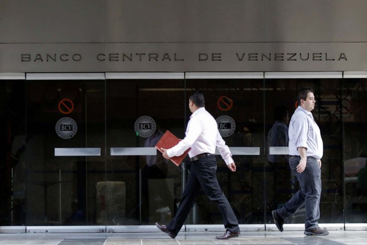 People walk past an entrance of the Venezuela's Central Bank in Caracas, Venezuela June 22, 2017. REUTERS/Marco Bello