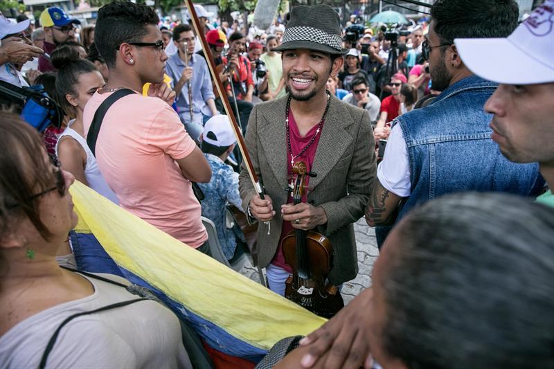 """El violinista Wuilly Arteaga (c), un músico que ganó popularidad en el país luego de que su instrumento terminara dañado en medio de una protesta opositora que se tornó violenta, se presenta junto a otros músicos frente a un centenar de personas hoy, domingo 4 de junio de 2017, en la Plaza Brión de Chacaíto, en Caracas (Venezuela). Decenas de venezolanos se manifestaron en Caracas a favor de la paz y en contra del Gobierno de Nicolás Maduro, mientras la coalición opositora Mesa de la Unidad Democrática (MUD) llamó a sus simpatizantes a participar mañana en un """"plantón"""" en varias vías del país. EFE/MIGUEL GUTIÉRREZ"""