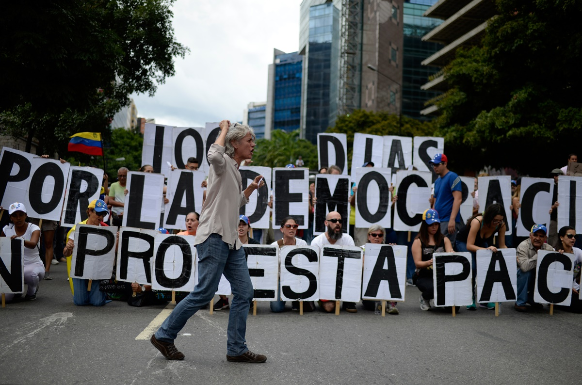 An opposition activist shouts slogans during a demonstration against Venezuelan President Nicolas Maduro in Caracas, on July 9, 2017. Venezuela hit its 100th day of anti-government protests on Sunday, one day after its most prominent political prisoner, Leopoldo Lopez, vowed to continue his fight for freedom after being released from jail and placed under house arrest. At least 91 people have died since non-stop street protests began on April 1. / AFP PHOTO / Federico PARRA