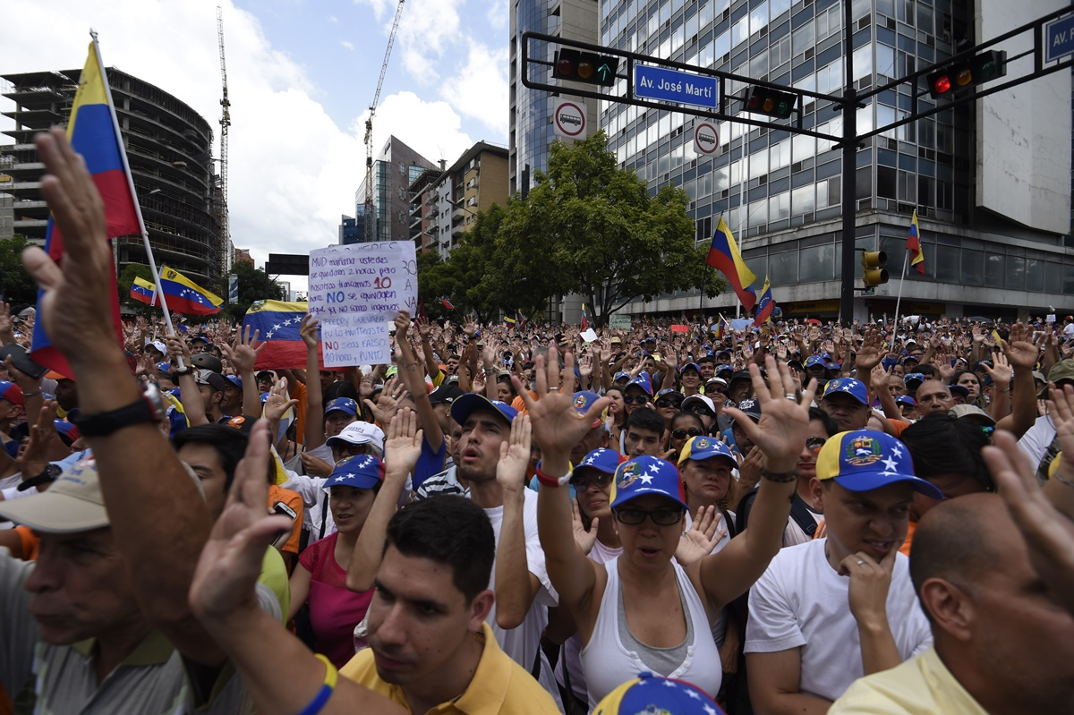 Opposition activists demonstrate against Venezuelan President Nicolas Maduro in Caracas, on July 9, 2017. Venezuela hit its 100th day of anti-government protests on Sunday, one day after its most prominent political prisoner, Leopoldo Lopez, vowed to continue his fight for freedom after being released from jail and placed under house arrest. At least 91 people have died since non-stop street protests began on April 1. / AFP PHOTO / Juan BARRETO