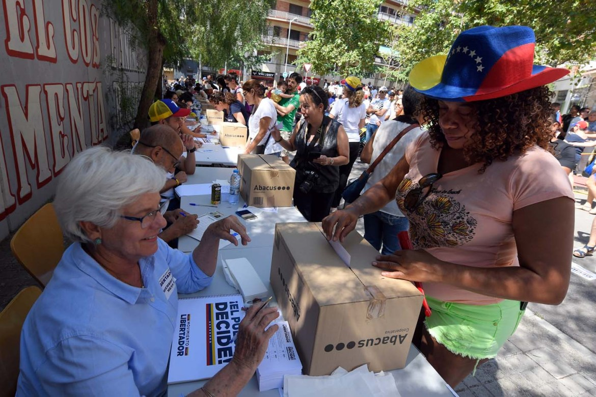 A Venezuelan resident in Barcelona casts her ballot during a symbolic plebiscite on president Maduro's project of a future constituent assembly, called by the Venezuelan opposition and held in Barcelona on July 16, 2017. / AFP PHOTO / LLUIS GENE