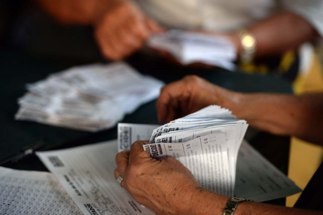 Volunteers count the ballots during an opposition-organized vote to measure public support for Venezuelan President Nicolas Maduro's plan to rewrite the constitution in Caracas on July 16, 2017. Authorities have refused to greenlight the vote that has been presented as an act of civil disobedience and supporters of Maduro are boycotting it. Protests against Maduro since April 1 have brought thousands to the streets demanding elections, but has also left 95 people dead, according to an official toll.  / AFP PHOTO / Federico Parra