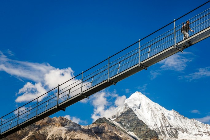 """A person walks on the """"Europabruecke"""",  supposed to be the world's longest pedestrian suspension bridge with a length of 494m, after the official inauguration of the construction in Randa, Switzerland, on Saturday, July 29, 2017. The bridge is situated on the Europaweg that connects the villages of Zermatt and Graechen. (Valentin Flauraud/Keystone via AP)"""