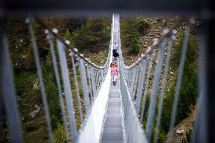 """People walk on the """"Europabruecke"""",  supposed to be the world's longest pedestrian suspension bridge with a length of 494m, after the official inauguration of the construction in Randa, Switzerland, on Saturday, July 29, 2017. The bridge is situated on the Europaweg that connects the villages of Zermatt and Graechen. (Valentin Flauraud/Keystone via AP)"""