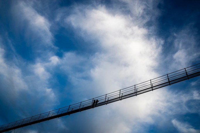 """A couple walks on the """"Europabruecke"""",  supposed to be the world's longest pedestrian suspension bridge with a length of 494m, prior to the official inauguration of the construction in Randa, Switzerland, on Saturday, July 29, 2017. The bridge is situated on the Europaweg that connects the villages of Zermatt and Graechen. (Valentin Flauraud/Keystone via AP)"""
