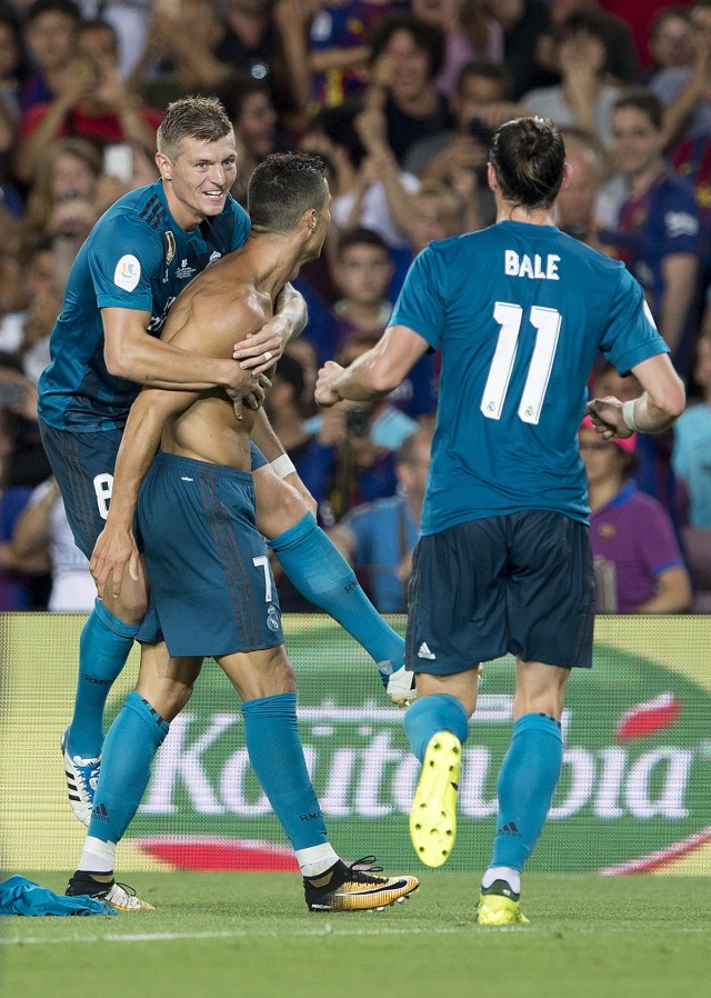 Real Madrid's Portuguese forward Cristiano Ronaldo (C) celebrates a goal with teammates Real Madrid's German midfielder Toni Kroos (L) and Real Madrid's Welsh forward Gareth Bale during the first leg of the Spanish Supercup football match between FC Barcelona and Real Madrid at the Camp Nou stadium in Barcelona, on August 13, 2017. / AFP PHOTO / Josep LAGO