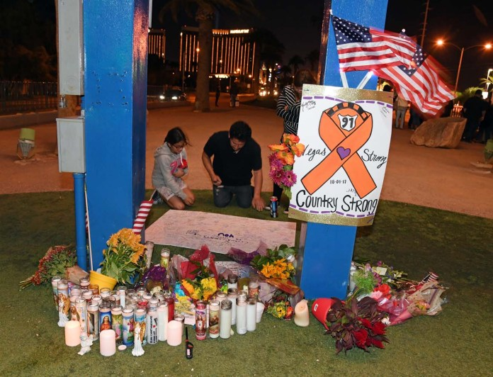 LAS VEGAS, NV - OCTOBER 03: People sign a poster at a makeshift memorial at the base of the Welcome to Fabulous Las Vegas sign in memory of the victims of Sunday night's shooting, on October 3, 2017 in Las Vegas, Nevada. Late Sunday night, a lone gunman killed at least 59 people and injured more than 500 after he opened fire on a large crowd at the Route 91 Harvest country music festival. The massacre is one of the deadliest mass shooting events in U.S. history.   Ethan Miller/Getty Images/AFP