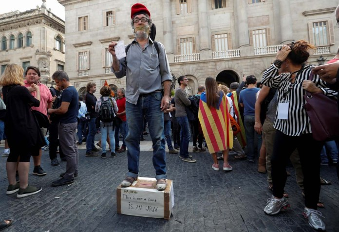 A man stages a performance in Plaza Sant Jaume after a protest called by pro-independence groups for citizens to gather at noon in front of city halls throughout Catalonia, in Barcelona, Spain October 2, 2017. REUTERS/Yves Herman