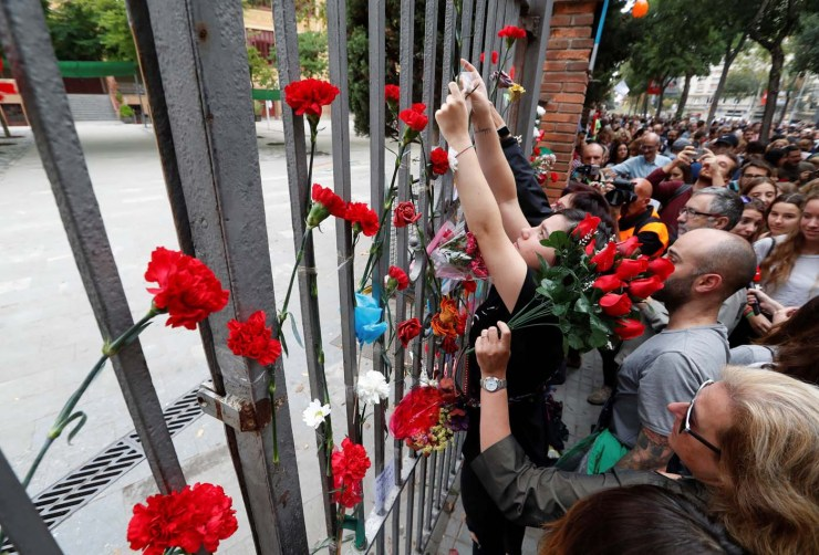 People place flowers on the gate of the Ramon Llull high school where Spanish police clashed with voters in the banned referendum in Barcelona, Spain October 3, 2017. REUTERS/Yves Herman