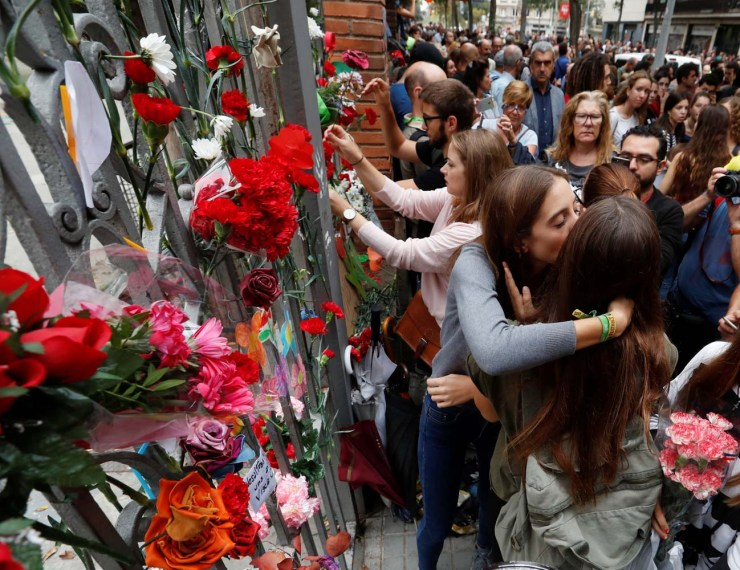 People place flowers on the gate of the Ramon Llull high school where Spanish police clashed with voters during the banned referendum in Barcelona, Spain October 3, 2017. REUTERS/Yves Herman