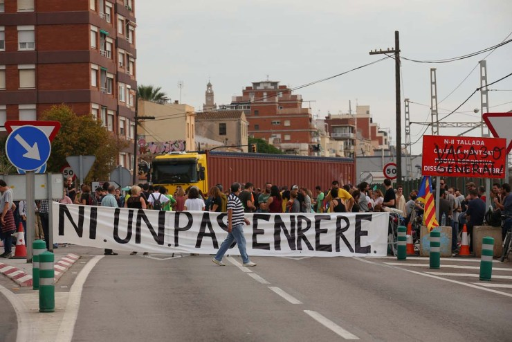 """People hold a banner reading """"No going back"""" as they block A2 road during a partial regional strike called by pro-independence parties and unions in El Masnou, Spain, October 3, 2017. REUTERS/Albert Gea"""