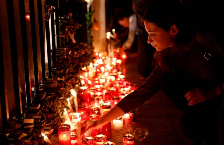 A woman places a candle on the Love monument during a silent candlelight vigil to protest against the assassination of investigative journalist Daphne Caruana Galizia in a car bomb attack, in St Julian's, Malta, October 16, 2017. REUTERS/Darrin Zammit Lupi TPX IMAGES OF THE DAY