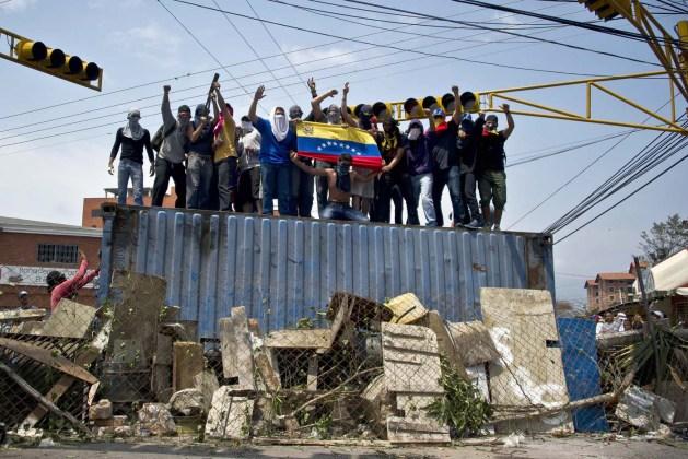 Manifestantes protestan contra el Gobierno de Maduro subidos a un contenedor en San Cristóbal. LUIS ROBAYO AFP