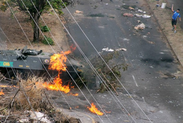 Demonstrator throws rocks at a National Guard tank on fire after being hit by a Molotov cocktail during a protest against President Maduro's government in San Cristobal