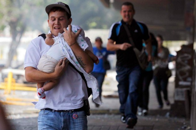 A man runs with a baby to take cover from teargas and stones during riots in Caracas